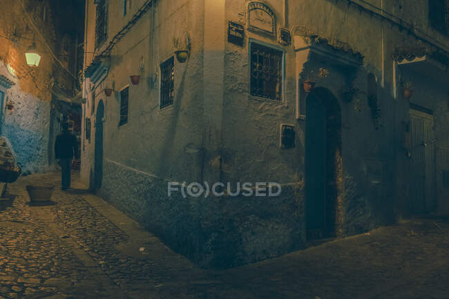 Person going on narrow street between ancient houses and corner of stone building in evening in Marrakesh, Morocco — Stock Photo
