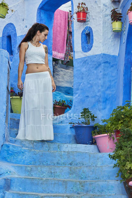 Красивая женщина, идущая между синими домами в Марракеше — стоковое фото