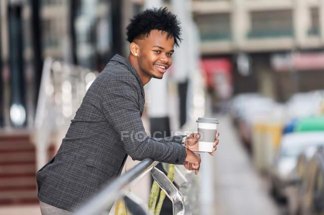Africano americano empresário com bebida quente inclinado sobre trilhos — Fotografia de Stock
