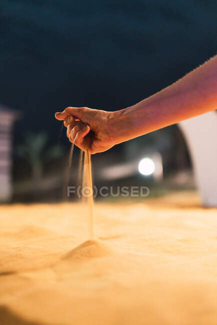 Crop hand spilling dry sand — Stock Photo