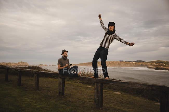 Jovem mulher feliz e homem em chapéus se divertindo no assento na costa perto do mar acenando e céu nublado — Fotografia de Stock