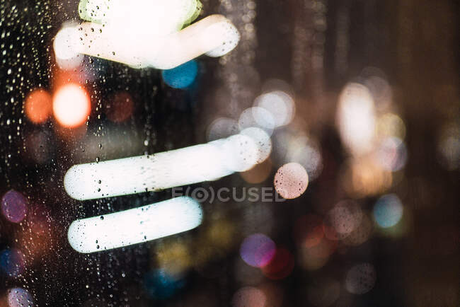 Night city through wet glass — Stock Photo