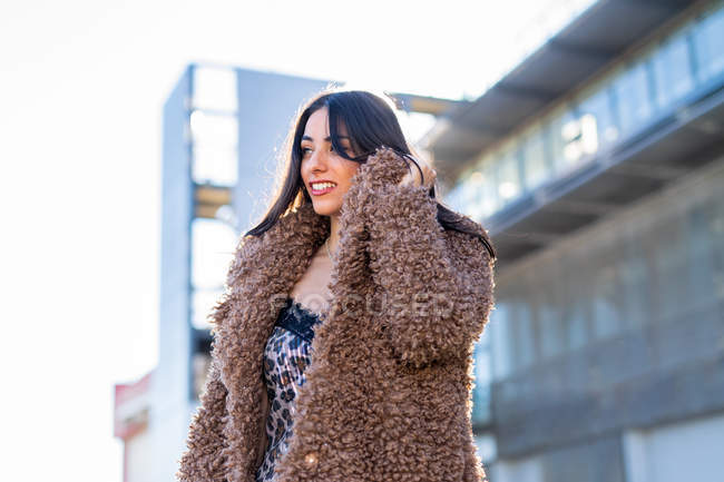 Cheerful woman wrapping in coat on street — Stock Photo
