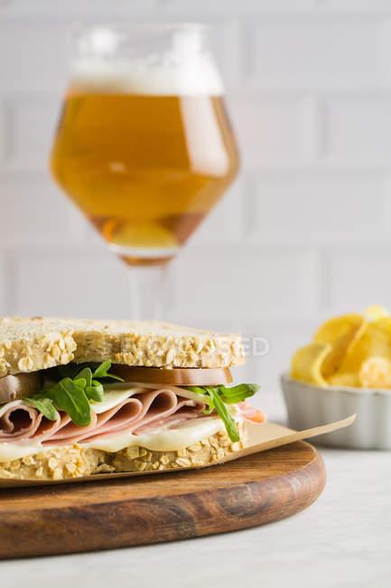 Köstliches Sandwich mit Schinken, Käse und Grüns mit Glas Bier und Chips auf weißem Hintergrund — Stockfoto