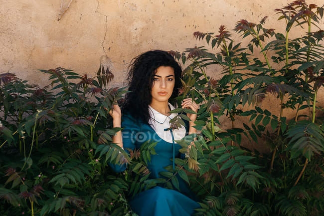 Beautiful young brunette Moroccan woman in blue gown standing between green plants growing near aged stone wall — Stock Photo