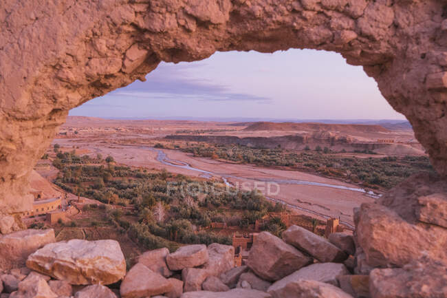 Rocks of high mountain with circle hole and picturesque view of valley with narrow river and desert in Marrakesh, Morocco — Stock Photo