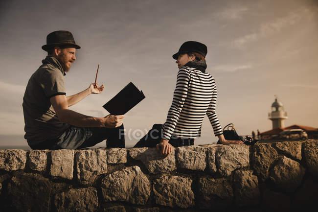 Vista laterale di ragazzo elegante in tubo cappello fumare e donna elegante in volume di lettura cap e seduto su rocce vicino al faro — Foto stock