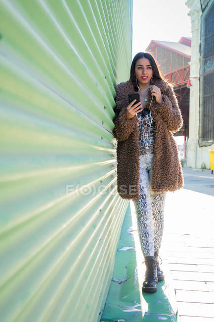 Woman in stylish outfit using smartphone while leaning on green wall on sunny day on city street — Stock Photo