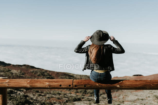 Back view of tourist woman sitting on wooden fence at the edge of the hill — Stock Photo