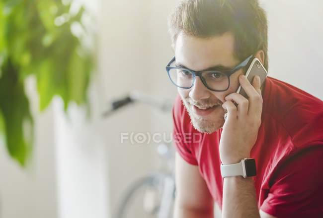 Young handsome bearded man in glasses talking on smartphone at home — Stock Photo