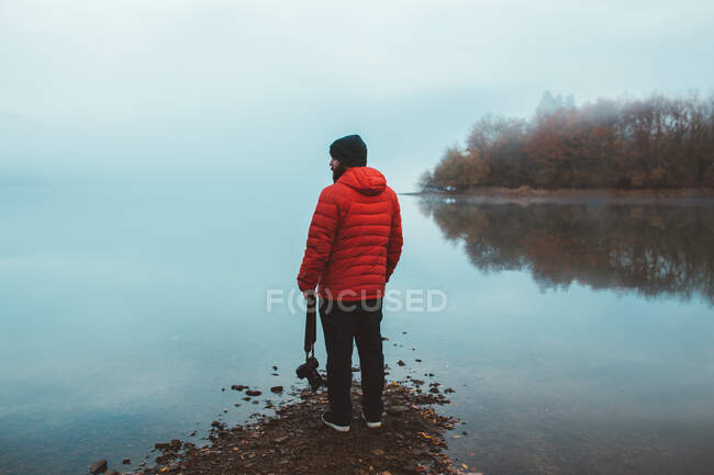 Tourist on empty lake shore in fog — Stock Photo
