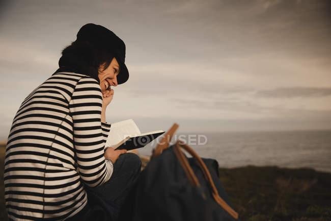Rückansicht einer eleganten Frau mit Mütze und Leseband, die auf einer Wiese in der Nähe von Leuchtturm am Ufer und herrlichem Himmel sitzt — Stockfoto