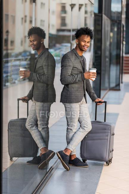 Homme d'affaires noir joyeux avec valise — Photo de stock