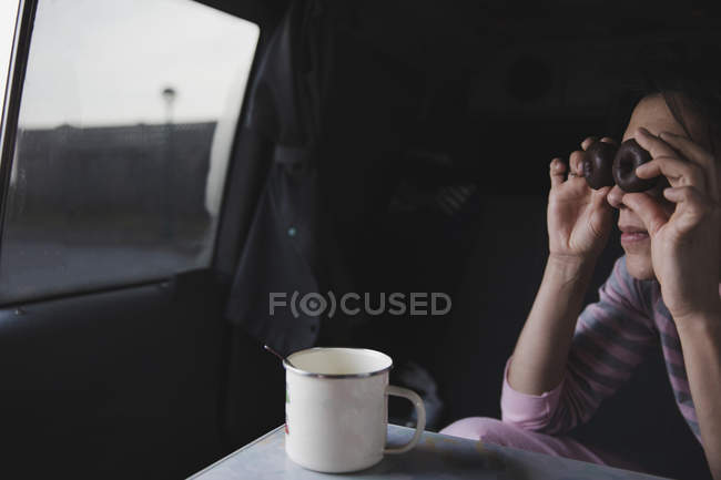 Woman looking through chocolate cookies and sitting in automobile near mug with spoon on table — Stock Photo