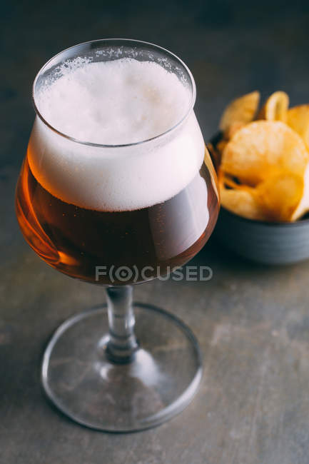Glass of beer and chips on dark grunge background — Stock Photo