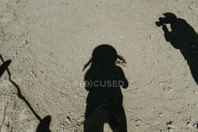 From above shadows of traveller and photographer on dry desert ground — Stock Photo