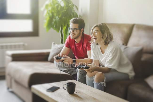 Young couple sitting on couch with gamepads and playing on console at home — Stock Photo