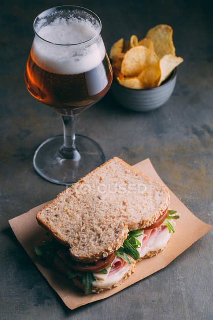 Delicious sandwich with ham, cheese and greens with glass of beer and chips on dark background — Stock Photo