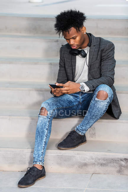 Black businessman with smartphone sitting on city street — Stock Photo