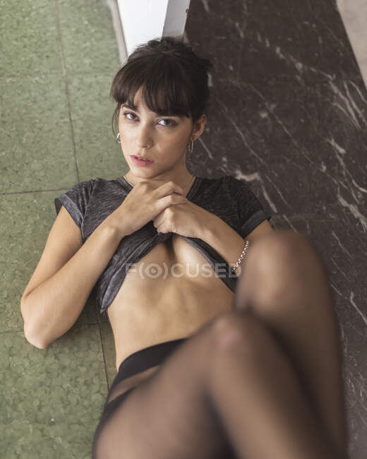 From above young attractive sensual lady in black tights and t-shirt with naked belly lying on floor — Stock Photo