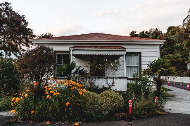 Facade of house near green plants on yard and blue sky in west neighborhood — Fotografia de Stock