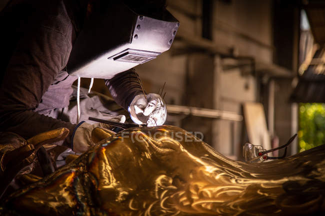 Man in welding helmet working with metal product on little foundry — Stock Photo