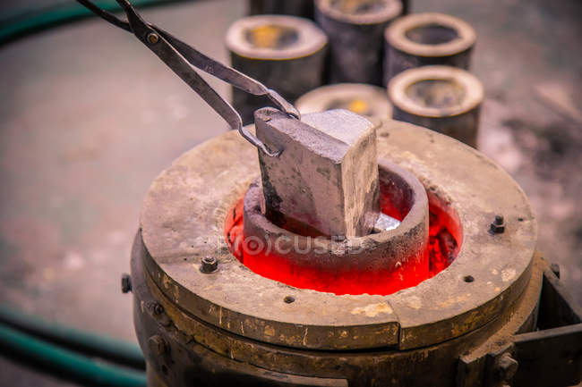 Closeup of metal product melting in crucible on little foundry on blurred background — Stock Photo