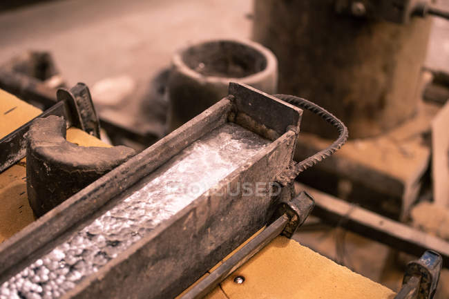Closeup of molten metal in form placed on table on little foundry on blurred background — Stock Photo