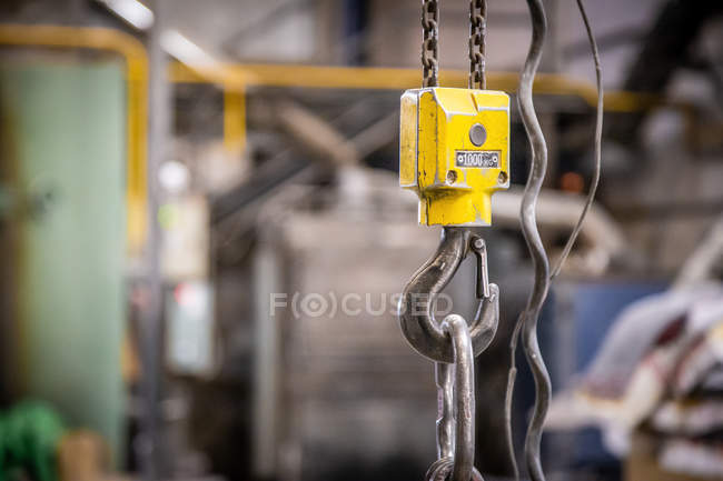Closeup of hoisting machine with iron chains on little foundry on blurred background — Stock Photo