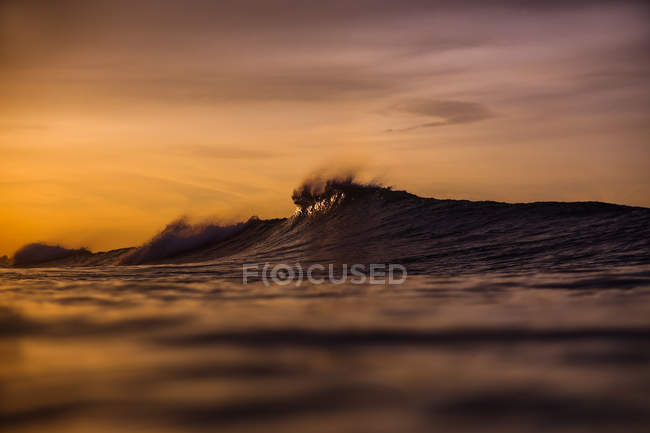 Closeup water wave of sea and cloudy sky at sunset — Stock Photo