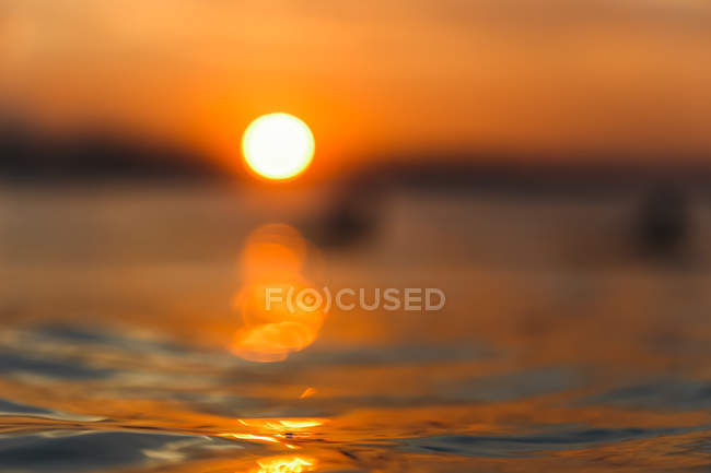 Gros plan de la surface de l'eau de mer avec des ondulations au coucher du soleil — Photo de stock