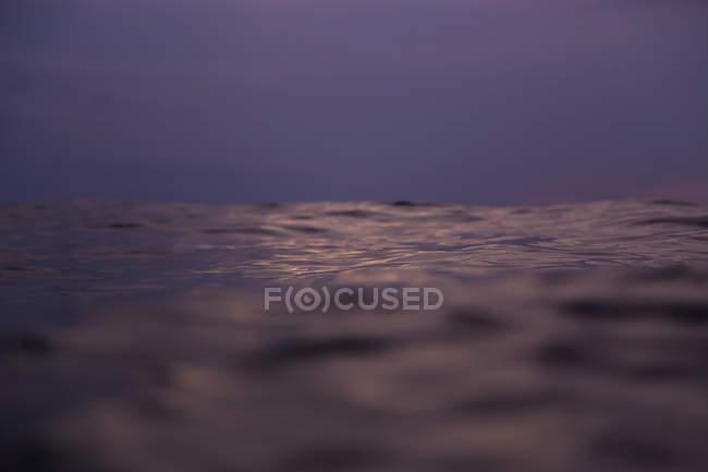 Primer plano de la ola de agua del mar y el cielo nublado - foto de stock
