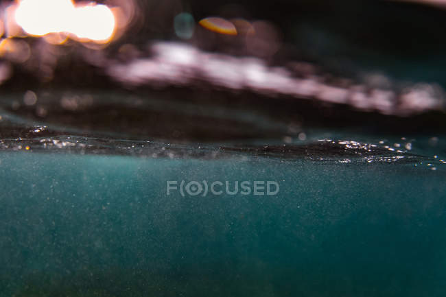 From below view of splashes in blue water of ocean — Stock Photo