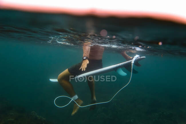 Side view of crop male floating on surf board in azure water of sea on Bali, Indonesia — Stock Photo