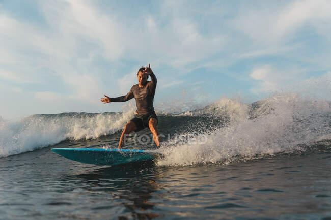 Surf maschile tra acqua di mare ondulata con spruzzi a Bali, Indonesia — Foto stock
