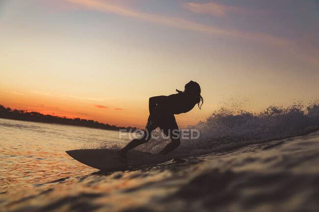 Male surfing between waving water of sea with splashes and cloudy sky in evening on Bali, Indonesia — Stock Photo