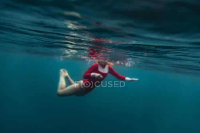 Seitenansicht einer Frau im roten Badeanzug beim Tauchen im blauen Meer auf Bali, Indonesien — Stockfoto