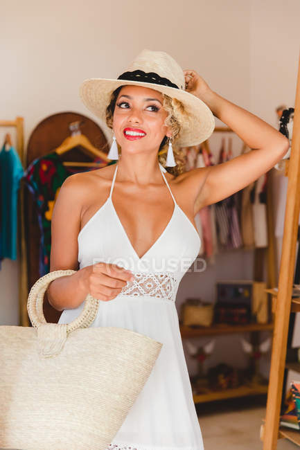 Stylish black young woman with hat and handbag standing in boutique — Stock Photo