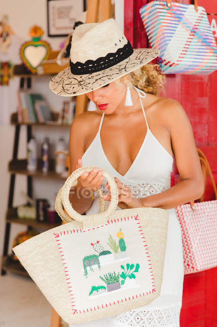 Stylish black young woman with hat and handbag shopping in boutique — Stock Photo