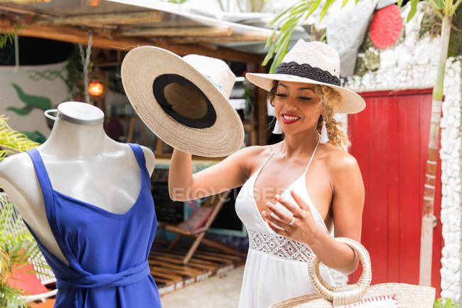Stylish black young woman with hat and handbag standing near mannequin in outdoor shop — Stock Photo