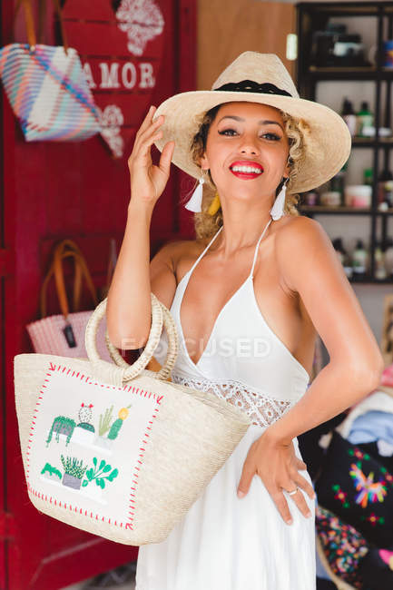 Portrait of stylish black young woman with hat and handbag standing in shop — Stock Photo