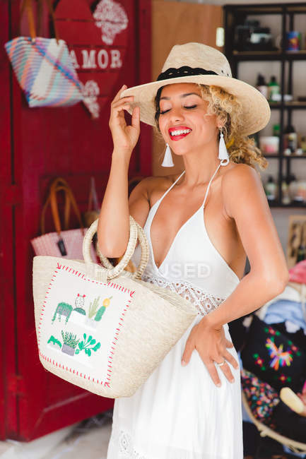 Smiling stylish black young woman with hat and handbag posing in shop — Stock Photo