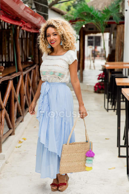 Portrait of stylish black young woman with curly hair and handbag standing on street in Mexico — Stock Photo