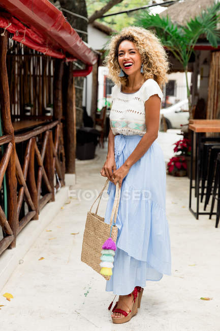 Portrait of cheerful stylish black young woman with curly hair and handbag standing on street in Mexico — Stock Photo