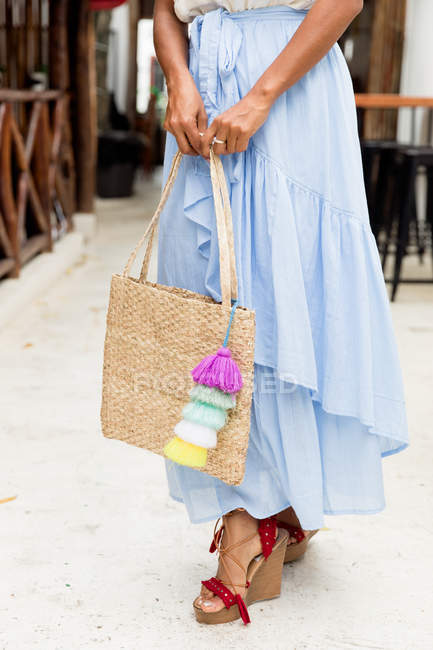Stylish woman in long blue skirt with handbag standing on street — Stock Photo