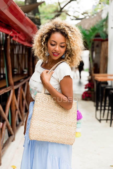 Stylish black young woman with curly hair and handbag posing on street in Mexico — Stock Photo