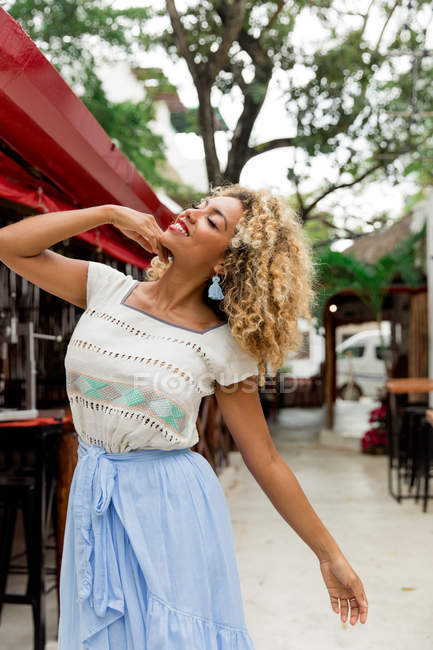 Positive black young woman with curly hair posing on street — Stock Photo