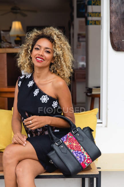 Portrait of stylish black young woman with curly hair and handbag in dress sitting on bench — Stock Photo
