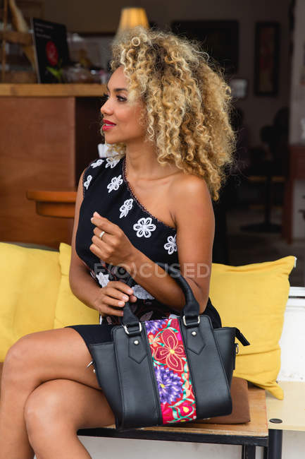 Stylish black young woman with curly hair and handbag in dress sitting on bench — Stock Photo