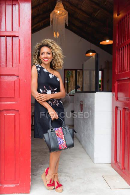 Sourire élégant noir jeune femme avec les cheveux bouclés et sac à main debout près de la porte rouge de la construction — Photo de stock
